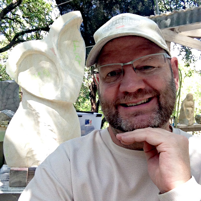 Dave taking a selfie with his sculpture Barn Martian in progress behind him.